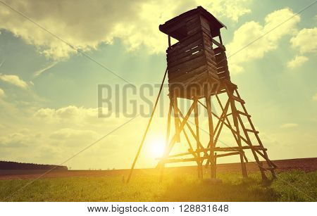 Lookout tower for hunting on meadow at setting sun.