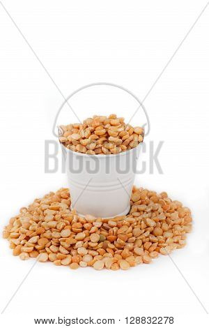 White bucket full of peas stands on a heap peas on a white background