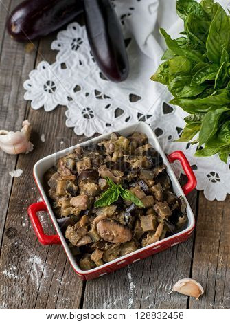 homemade stewed egglpants with mushrooms on vintage wooden background