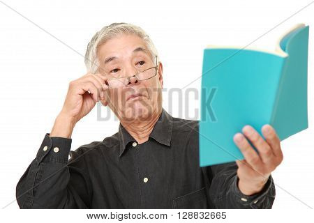 portrait of senior Japanese man with presbyopia on white background