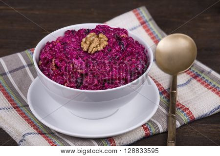 Fresh salad with beet and walnuts on white plate. Close up