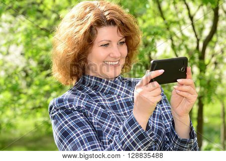 Woman using cell phone in the park