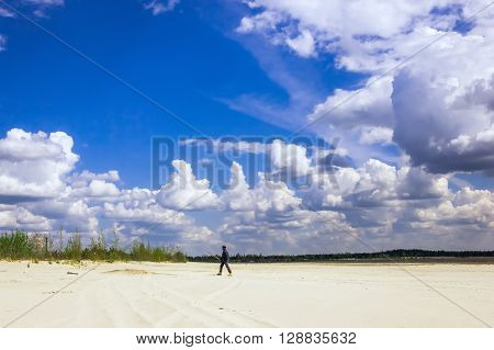 Man in a turban walking on sandy plains under a sky with cumulus clouds on a sunny day.