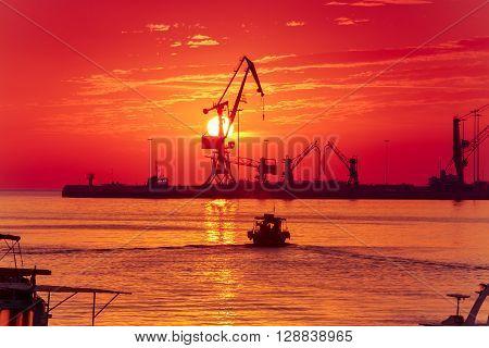 Cranes in sea cargo port of Heraklion on the background of the rising sun, Crete, Greece.