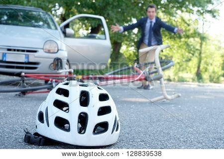 driver coming out from his car to assist aching man after bicycle accident on the asphalt