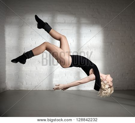 Female dancer flying in a beautiful pose. Illusion.