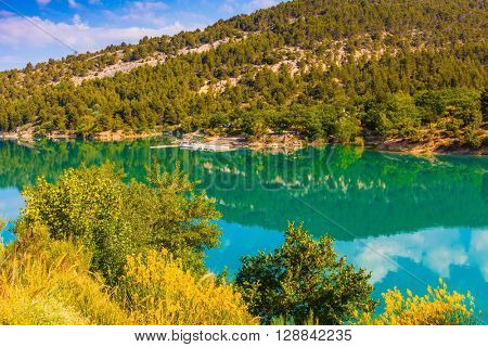 Mountain canyon Verdon in the French Alps. Smooth water of the river reflects the cloudy sky and wooded shore