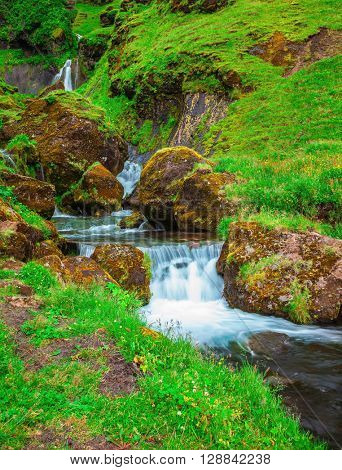 Gorgeous cascading waterfall from melting glacier. Basalt mountains covered in green grass and moss. Iceland
