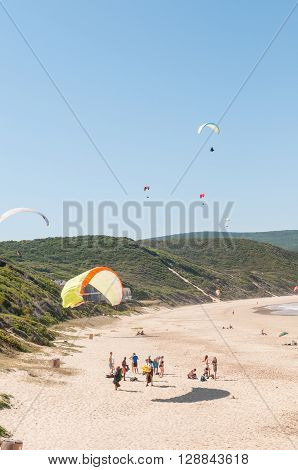 KNYSNA SOUTH AFRICA - MARCH 3 2016: Paragliders in the air while beachgoers enjoy the sun at a beach in Buffelsbaai (Buffalo Bay) a small town in the Knysna municipal area