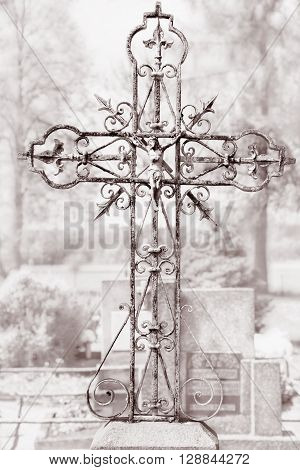 Metal crucifix on an old metal cross in a cemetery in black white
