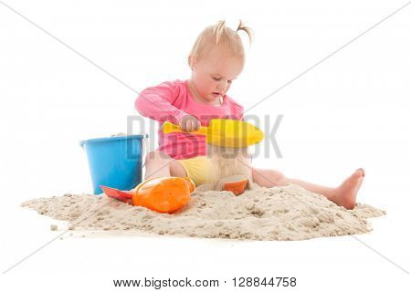 Little toddler playing in the sand isolated over white background