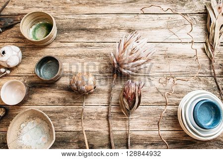 Flat lay set of handmade modern ceramic crockery. Top view of unusual creative bowls with rare dry flowers on  old wooden background. Beige and blue empty ceramics over wooden table with free space