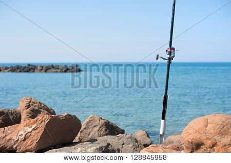 Fishing Pole With Red Reel On Blue Sea