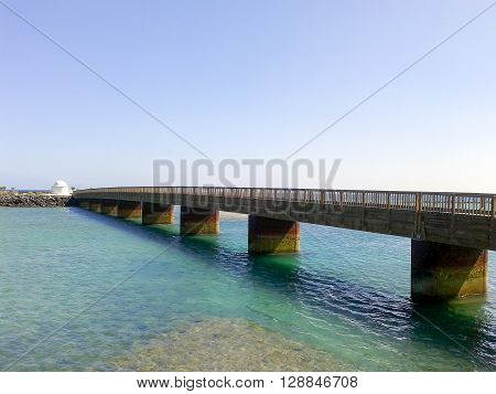 A shot in perspective of a bridge in the sea