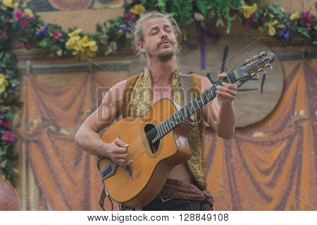 Man With Medieval Costume Singing And Playing Guitar