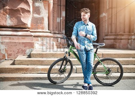 Positivity in mind. Cheerful delighted smiling guy holding  bicycle and going to ride it while spending time outdoors