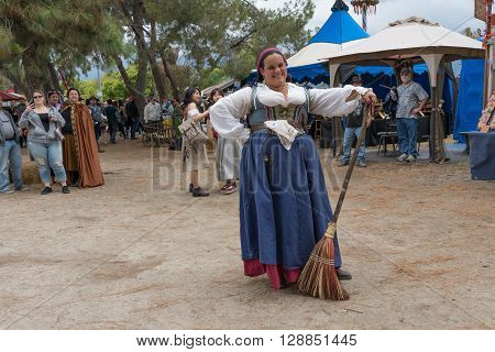 A Woman With A Medieval Costume Holding A Broom
