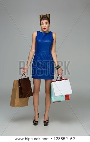 Confused young woman in blue dress with multiple shopping bags. Guilty expression. Over grey background. Copy space.