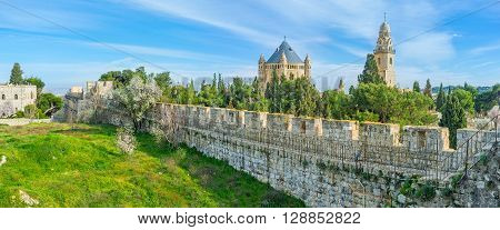 Panorama of the city wall surrounded by lush greenery with the Dormition Abbey among the pines Jerusalem Israel.