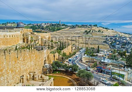JERUSALEM ISRAEL - FEBRUARY 18 2016: The huge city ramparts and the grey dome of Al-Aqsa mosque with the Olive Mount on the background on February 18 in Jerusalem.