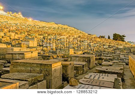 JERUSALEM ISRAEL - FEBRUARY 18 2016: The evening view of the medieval Jewish cemetery on the Mount of Olives on February 18 in Jerusalem.