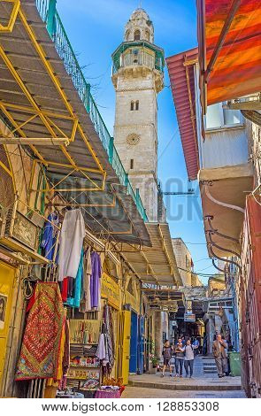 JERUSALEM ISRAEL - FEBRUARY 18 2016: The Arab bazaar with the wide range of traditional goods with the Omar Mosque on the background on February 18 in Jerusalem.