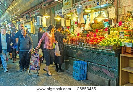 JERUSALEM ISRAEL - FEBRUARY 18 2016: The hasidic family chooses fresh and tasty fruits and vegetables in Mahane Yehuda market on February 18 in Jerusalem.