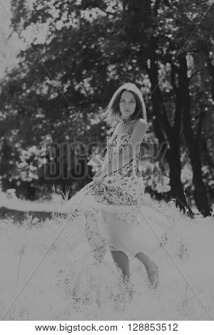 Young brunette woman in a white dress. A girl stands in the middle of pink flowers field on a sunny day. Field flowers beauty nature - The concept of country vacation. Article about vacation.