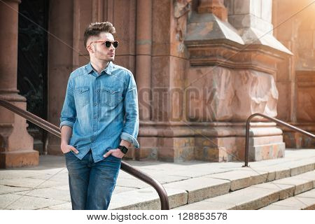 Modern vision. Pleasant confident handsome man looking aside and holding his hands in pockets while leaning on the handrail