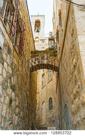The tiny backstreet with the stone prop supporting the medieval houses' walls and the belfry of the church on the background Jerusalem Israel.