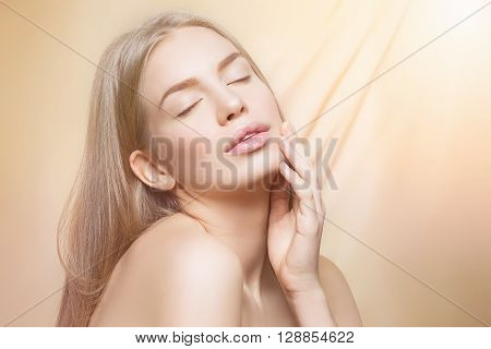 Beautiful young woman with perfect skin and shiny hair touching face over beige background. Beauty shot. Copy space.