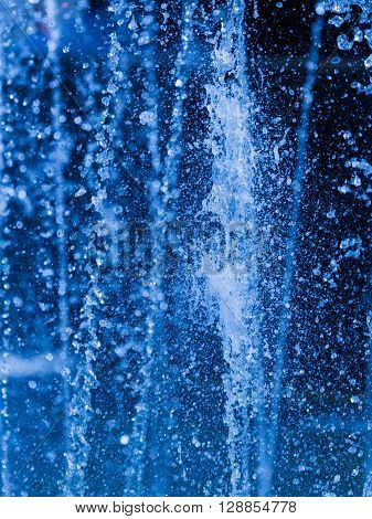 beautiful clear blue water jets that flow and bubbling and splashing in the fountain