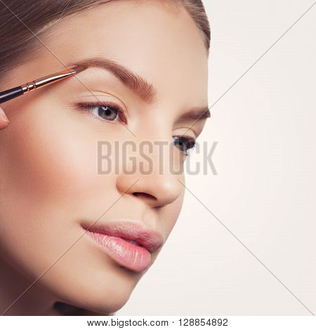 Beautician correcting eyebrows form on beautiful woman face. Beauty shot. Close-up. Isolated. Copy space. Square composition.