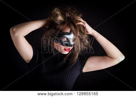 a girl with red lips and loose long hair in a black mask