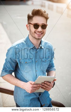 Brighten your live. Cheerful delighted handsome guy smiling and holding tablet while leaning on the handrail