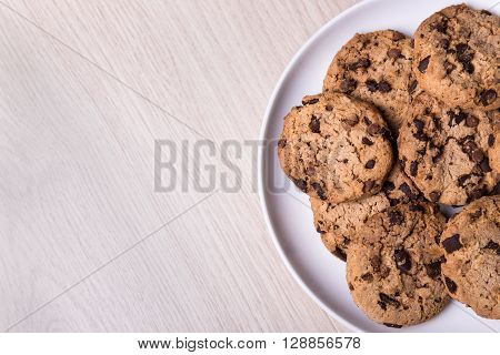 Top View Of Chocolate Chip Cookies On White Plate And Copy Space On Wooden Table