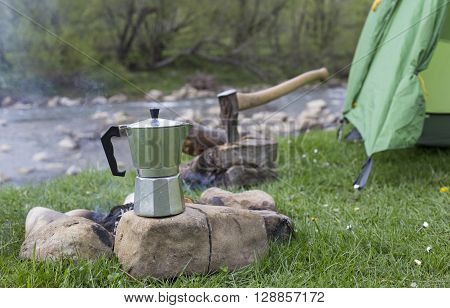 Mug Stands On A Log Near The Fire At A Campsite.