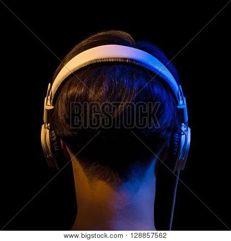 head of a teenager in headphones in blue and orange light