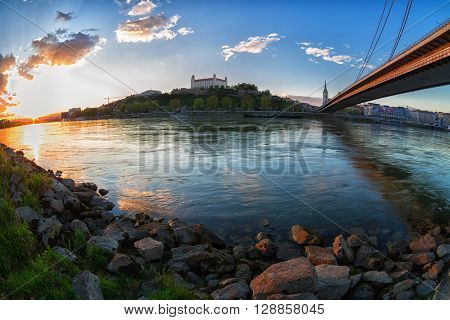 A view of the Bratislava castle and bridge from the bank of the Danube River at sunset Slovakia. Fisheye.