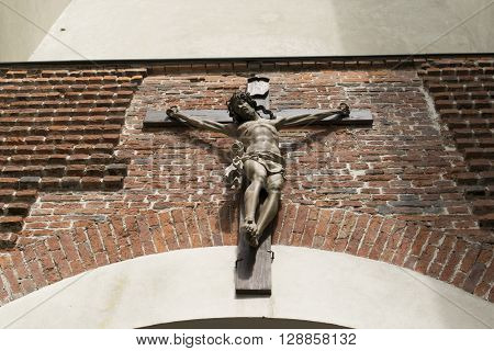 Crucifix on wall of church or cathedral. Jesus Christ on cross. Religion, belief and hope. Holy and sacred places.