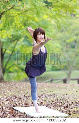 Japanese woman outside doing yoga Lord of the Dance Pose