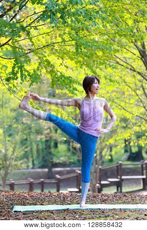 Japanese woman outside doing yoga Extended Hand-To-Big-Toe Pose ** Note: Soft Focus at 100%, best at smaller sizes