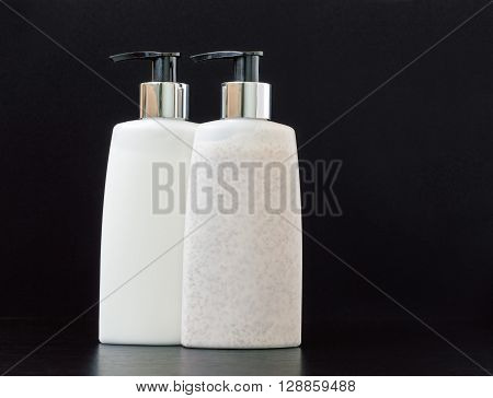 Skin exfoliation cream and makeup remover lotion in pump plastic bottles on a dark table.