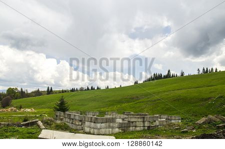Green fields and meadows with ruins of an ancient castle. Summertime vacation sites - somewhere in Carpathian mountains (traveling to Ukraine)