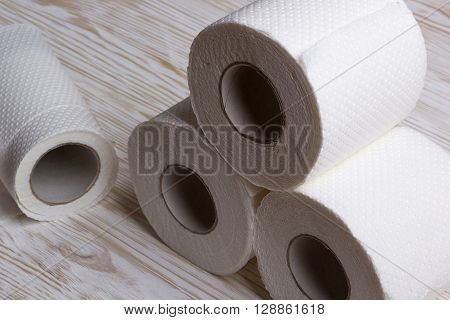 Rolls of toilet paper on wooden board