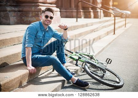 Live life fully. Cheerful handsome smiling guy sitting on the footsteps   near his bicycle and resting while feeling delighted