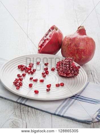 Pomegranate whole, half and seeds on white plate. Vertical image with back lighting. Shallow depth of field.