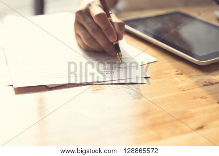 Man's Hand Signing Application Form With Tablet On Wooden Table