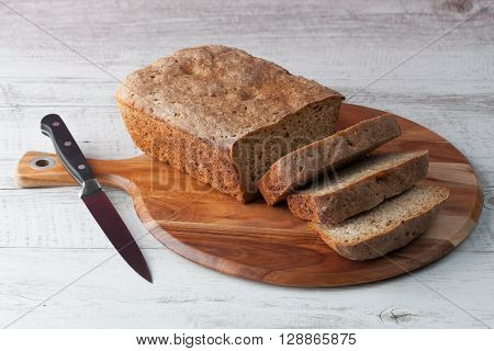 Homemade dark rye sourdough bread on wooden chopping board with kitchen knife