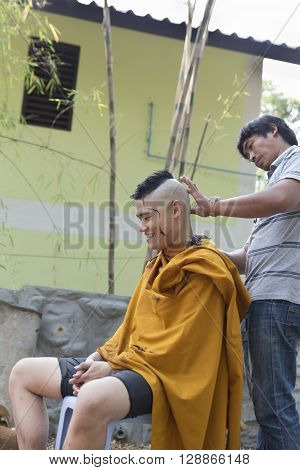 CHIANG MAI, THAILAND - APRIL 30: man shave man's hair before buddhist monk ordination ceremony at Umong temple in Chiang Mai Thailand on April 30 2016.